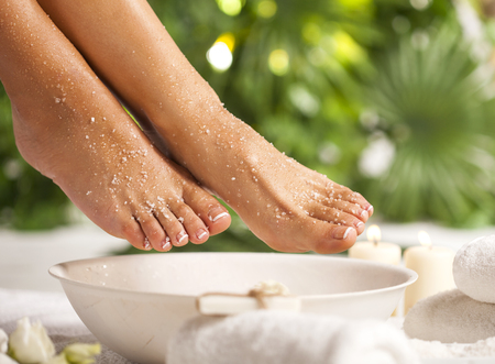 Female feet with sea salt on white floor and tropical green leaves Stockfoto