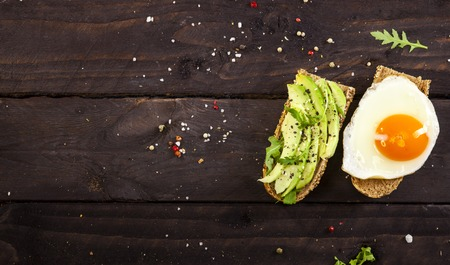 Closeup of two different bruschettas with avocado, rucola sesame, seeds, egg on a wooden table.