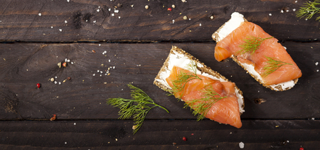 Closeup of bruschettas with cream cheese, salmon and dill on a wooden table.