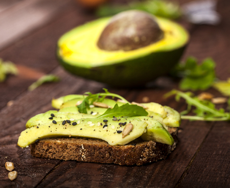 Closeup of bruschetta with avocado, rucola sesame and seeds on a wooden table.