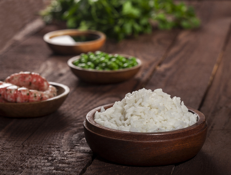 Cooked white rice in wooden bowl with shrimps, peas on a wood brown background.