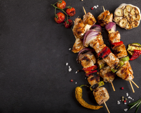 Grilled chicken skewers with spices and vegetables on a stone black background. Top view with copy space Stock Photo