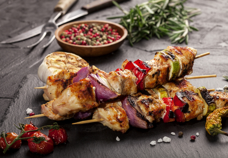 Grilled chicken skewers with spices and vegetables on a black background.
