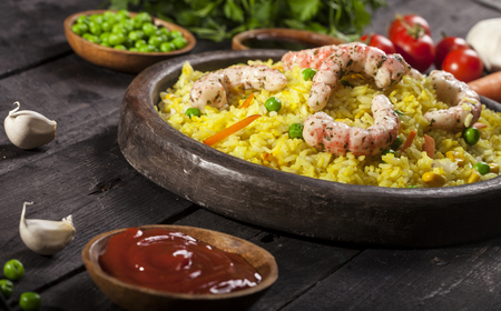 Cooked white rice with shrimps, curry and vegetables in a dish on a wood black background. Standard-Bild