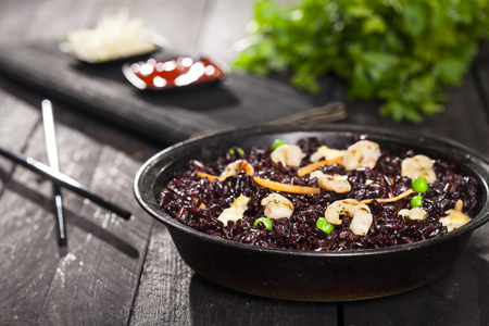 Cooked black rice with shrimps and vegetables in dish on a wood black background. 免版税图像 - 121847976