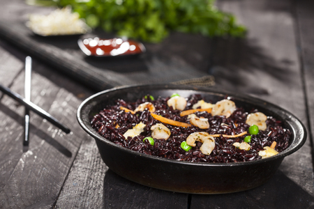 Cooked black rice with shrimps and vegetables in dish on a wood black background.