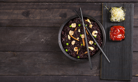 Cooked black rice with shrimps and vegetables in dish on a wood black background. Top view with copy space