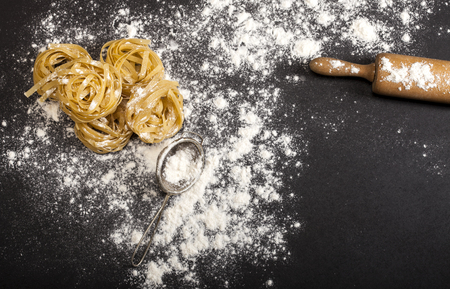 Italian traditional raw pasta on the black stone background. Top view with copy space