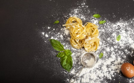 Italian traditional raw pasta with basil and egg on the black stone background. Top view with copy space