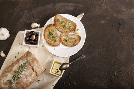 Sliced traditional toast bread with olive oil, olives, garlic and herbs on a white napkin and dark table with copy space. Top view.