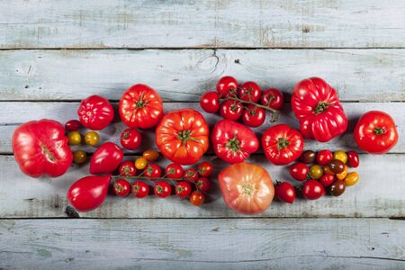 Tomatoes on rustic blue wooden background top view copy space. Standard-Bild