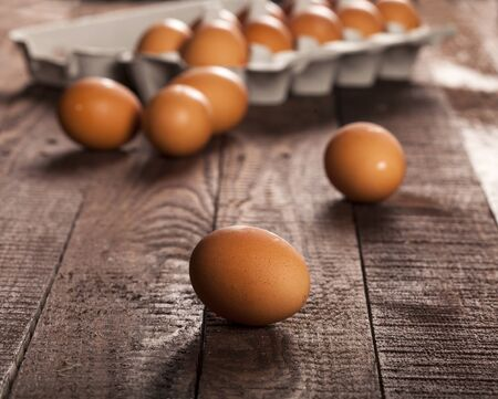 Brown eggs in a box on dark rustic table background. Imagens