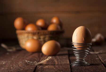 Brown eggs in a basket on dark rustic table background.