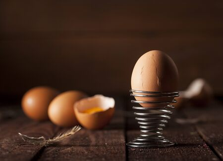Brown eggs and broken egg with yolk on dark rustic table background. Imagens