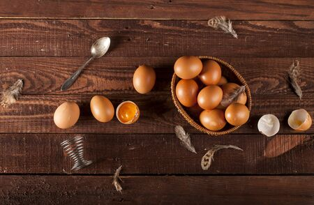 Brown eggs in a basket, broken egg with yolk and feather on dark rustic table background. Top view.