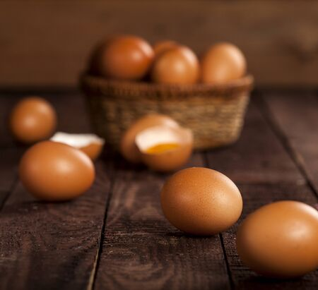 Brown eggs in a basket and broken egg with yolk on dark rustic table background. Imagens