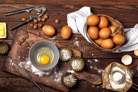 Ingredients for the preparation of bakery products: flour eggs butter hazelnuts cocoa. Top view. Rustic style. Brown wooden background. Imagens