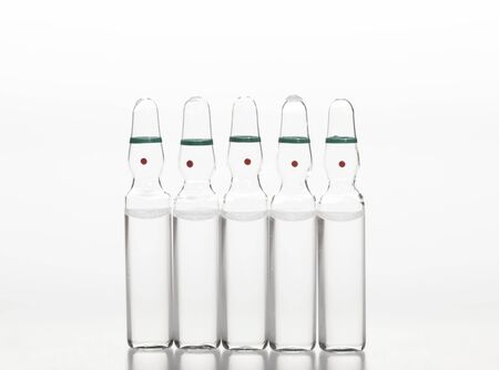 Glass medicine ampoules with liquid on white background