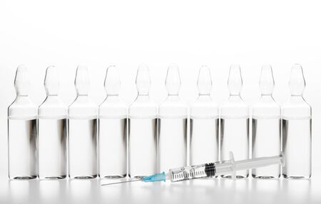 Glass medicine ampoules with liquid and syringe on white background