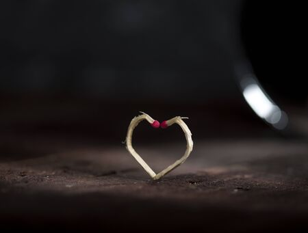 Two matchsticks made in the shape of a heart ob dark background. Love concept.