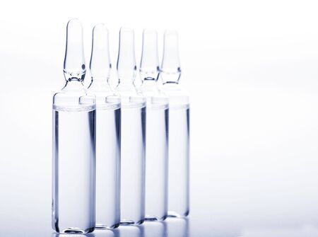 Glass medicine ampoules with liquid on white Stock Photo