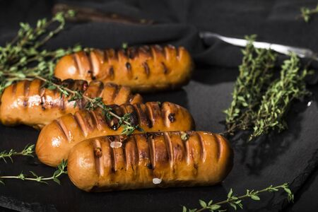 Sausages with thyme on a black background. Stock Photo