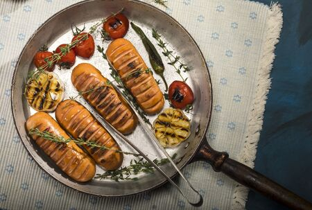 Sausages with thyme and vegetables in old pan on white napkin and blue background. Top view. Stock Photo