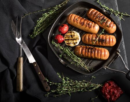 Sausages with thyme and vegetables in a pan on black background. Top view.