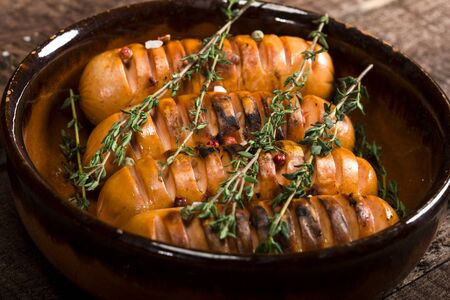 Sausages with thyme in a pan on a wooden background.