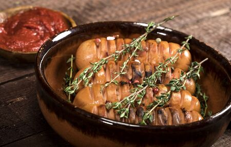 Sausages with thyme in a ceramic pan on a wooden background.