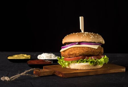 Fresh delicious burger with meatball, cheese, tomato, onion and lettuce on black background with copy space