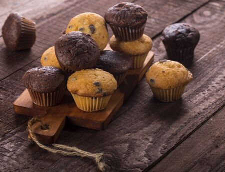 Assorted fresh delicious muffins on a wooden background.