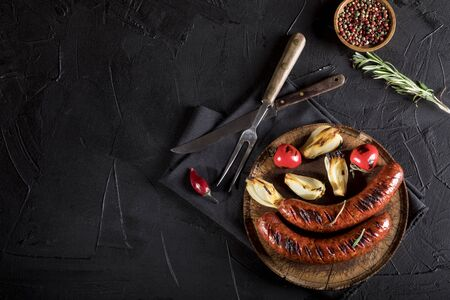 Grilled sausages with spices on black background. Top view with copy space. Standard-Bild