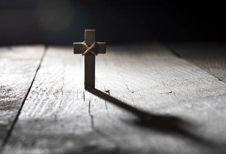 Cruz de madera sobre fondo de madera oscura con espacio de copia.