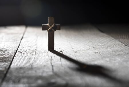 Wooden cross on dark wooden background with copy space.