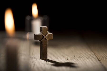 Wooden cross and candles on dark wooden table.