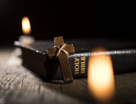 Old Holy Bible, wooden cross and candles on wooden background.