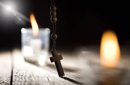 Rosary Beads and candle on wooden background. Stock Photo