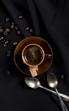 Coffee cup, spilled coffee beans and spoons on a black background. Top view. Banque d'images