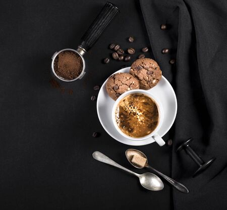 Coffee, cookies and utensils for coffee maker on black background with copy space for text