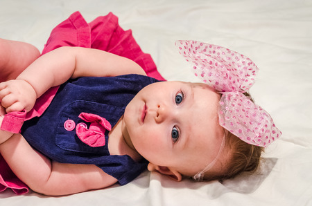 bed skirt: Portrait of a baby girl in a dress with diapers with a bow on her head which lies on the bed