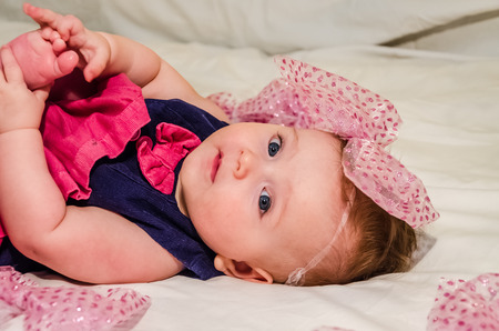 bed skirt: Portrait of a baby girl in a dress with diapers with a bow on her head which lies on the bed in her room