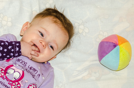 bed skirt: Portrait of a little baby girl who lies with a ball and smiling