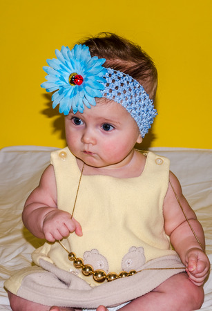 bed skirt: Portrait of a beautiful little baby girl in a yellow dress with a bow on her head and jewelry beads around his neck