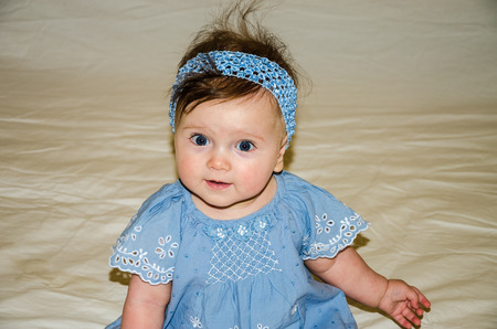 bed skirt: Portrait of the beautiful sweet little baby girl in a blue dress with a hairpin on the head that smiles Stock Photo