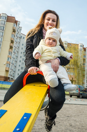playground ride: Young beautiful mum ride on a swing with a baby girl at the playground Stock Photo