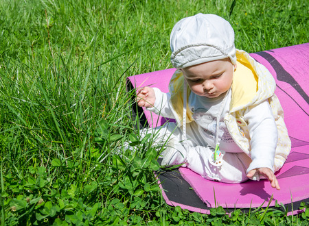 karemat: Little girl baby playing in the grass in a meadow sitting on karemat Stock Photo