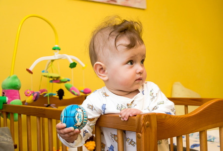bebe cuna: Little girl playing ball in the baby crib
