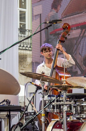 playing the market: Lviv Ukraine June 2015: Alfa Jazz Fest 2015. Musician Contrast Trio band playing bass on stage jazz festival on the Market Square in Lviv near the town hall Editorial