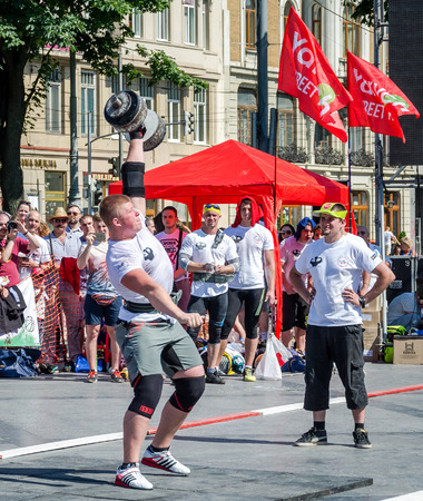 strongman: Lviv, Ukraine - July 2015: Yarych street Fest 2015. Strongman competitions raises dumbbell hand